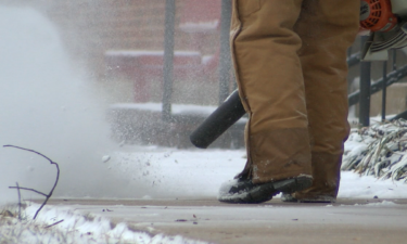 A Jefferson City man uses a leaf blower to clear a layer of snow off of a sidewalk on Monday.