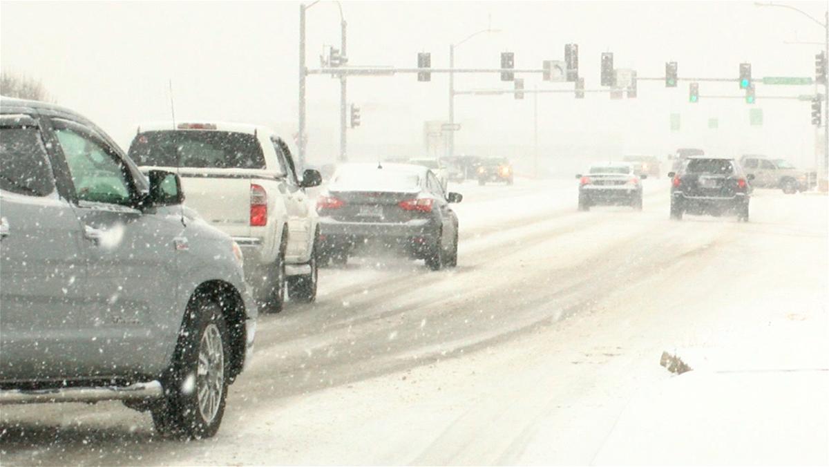 Vehicles navigate Truman Boulevard in Jefferson City as snow falls on Jan. 20, 2020.