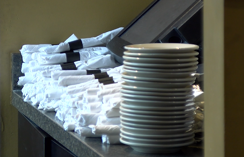 Rolled silverware sit in a restaurant.