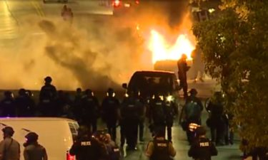Protesters set fire to a police car in Kansas City.