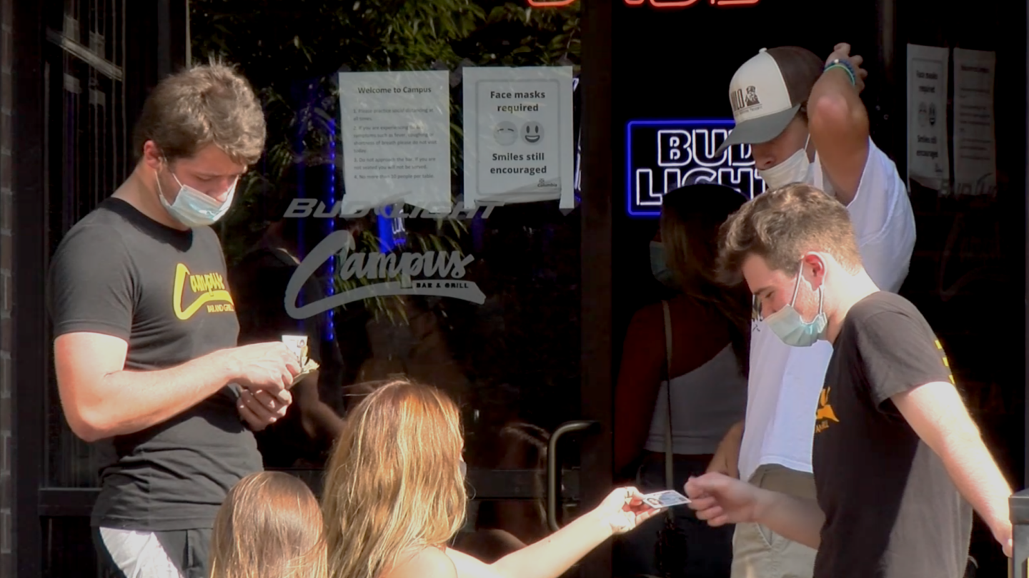 Patrons gather outside Campus Bar & Grill in downtown Columbia.