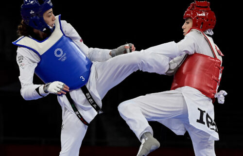 Refugee Olympic Team's Kimia Alizadeh (Blue) and Iran's Nahid Kiyani Chandeh (Red) compete in the taekwondo women's -57kg elimination round bout during the Tokyo 2020 Olympic Games at the Makuhari Messe Hall in Tokyo on July 25.