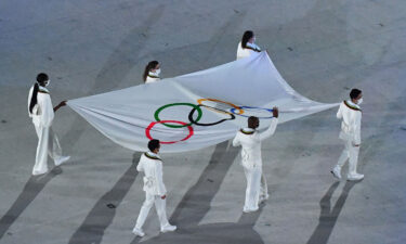 The Olympic flag is seen being carried during the opening ceremony of the Tokyo 2020 Olympic Games at the Olympic Stadium in Tokyo on July 23.