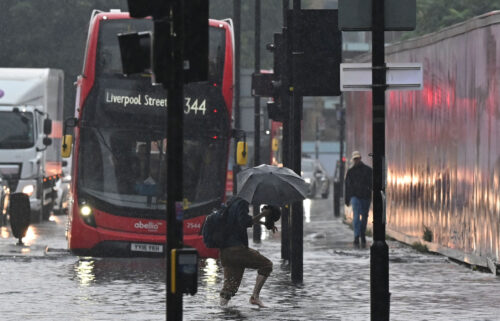 A pedestrian crosses through deep water on a flooded road in London on July 25. Climate and infrastructure experts have been warning for years that London