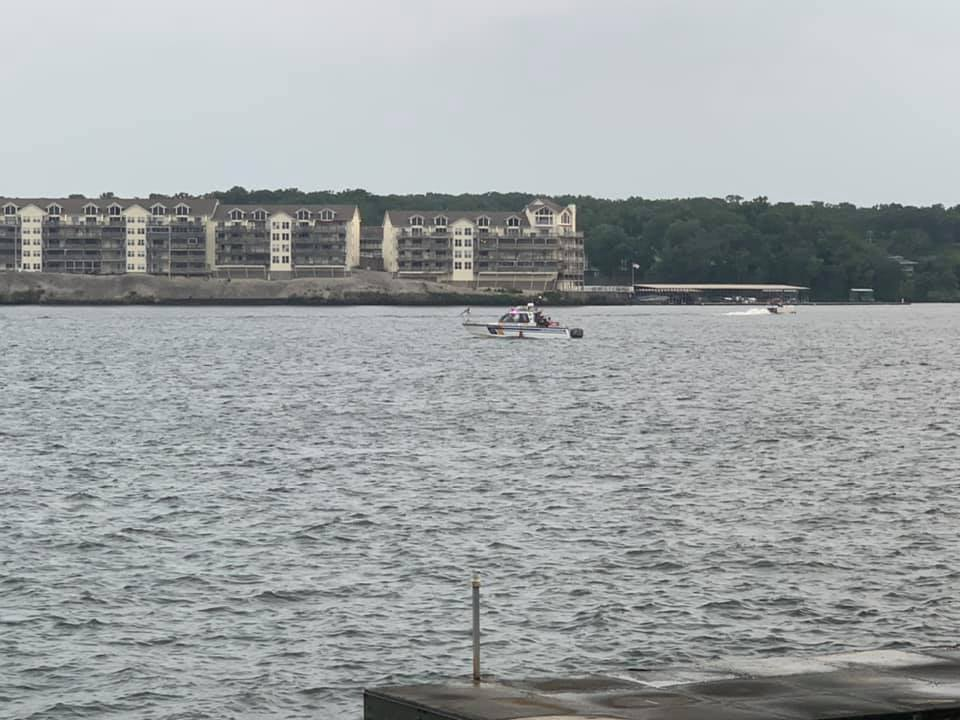 A boat searches for a missing swimmer on the Lake of the Ozarks on Sunday, Aug. 8, 2021.
