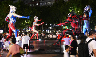 People watch sculptures of Ultraman and a monster outside a shopping center on July 17 in Chongqing