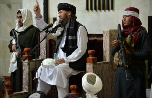 Armed Taliban fighters stand next to a Mullah