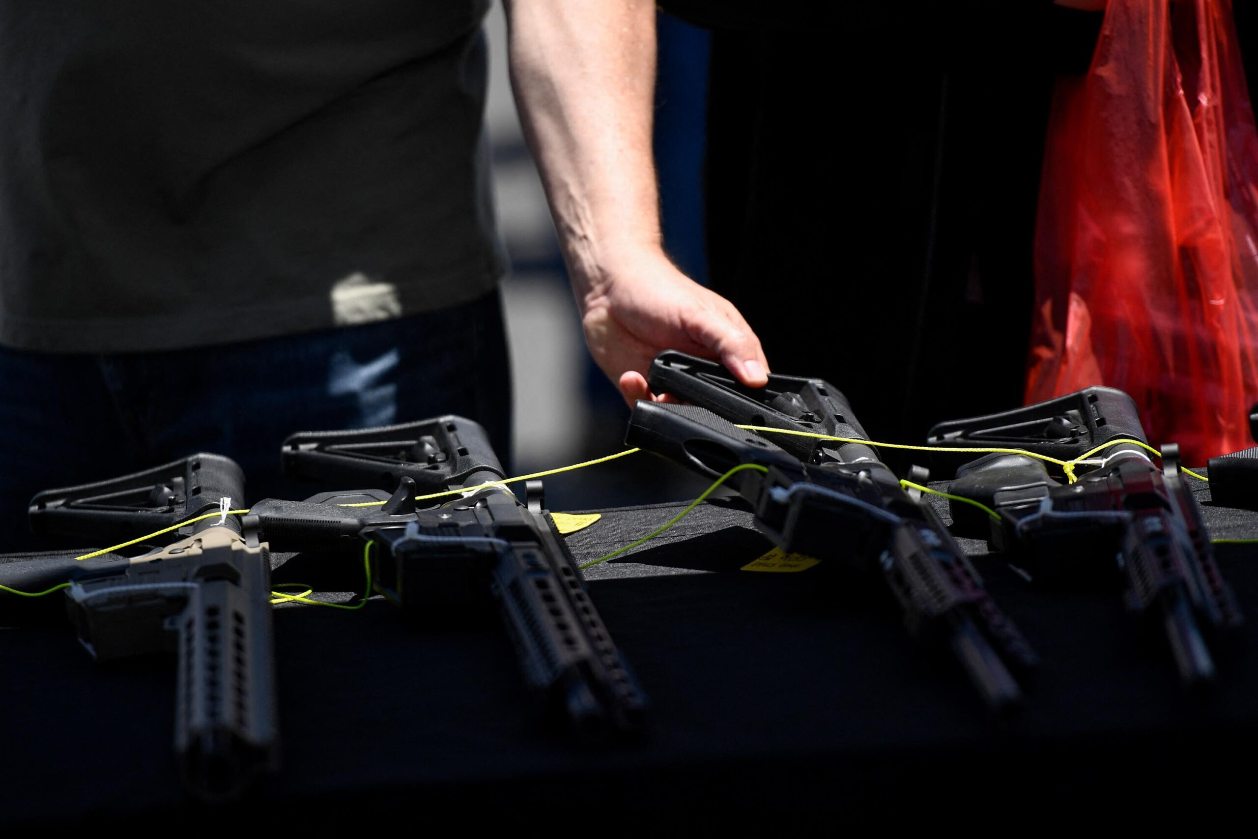 <i>PATRICK T. FALLON/AFP/Getty Images</i><br/>A customer examines a California-compliant AR-15 style rifle displayed for sale at a vendor booth at a gun show in Costa Mesa