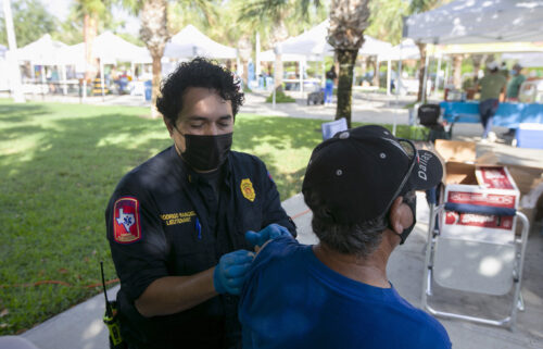Brownsville Fire Department lieutenant Rodrigo Rangel places a bandage over Homero Ortega's vaccine injection spot at the City of Brownsville's Department of Public Health's popup COVID-19 vaccine clinic
